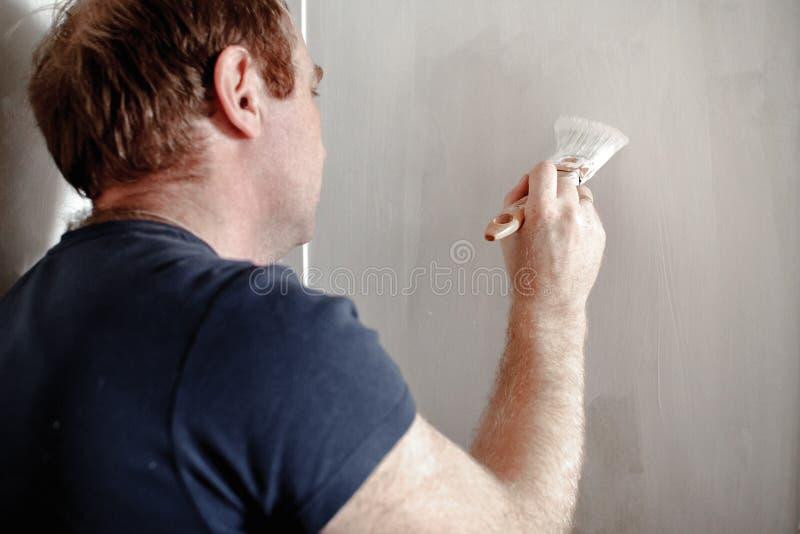 一个人绘有白色油漆的墙壁在公寓 修理您的家 图库摄影