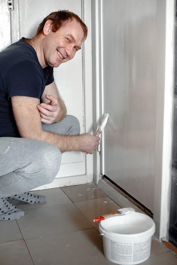 一个人绘有白色油漆的墙壁在公寓 修理您的家 免版税库存图片