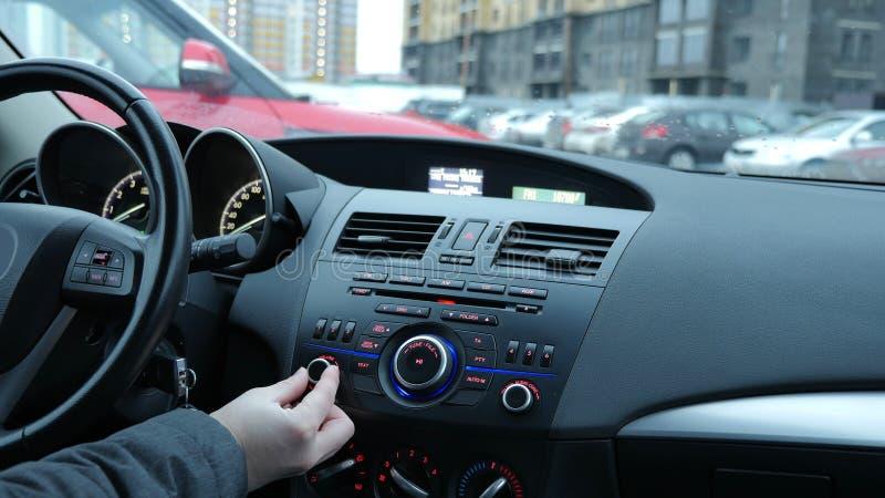 一个人调整无线电接收机并且调整在汽车的容量 免版税库存图片