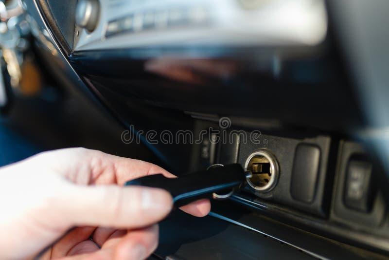 一个人连接设备到汽车的香烟打火机 T 免版税库存图片