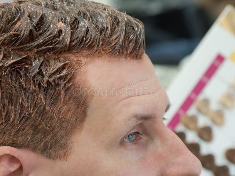 一个人选择油漆染他的头发 免版税库存图片