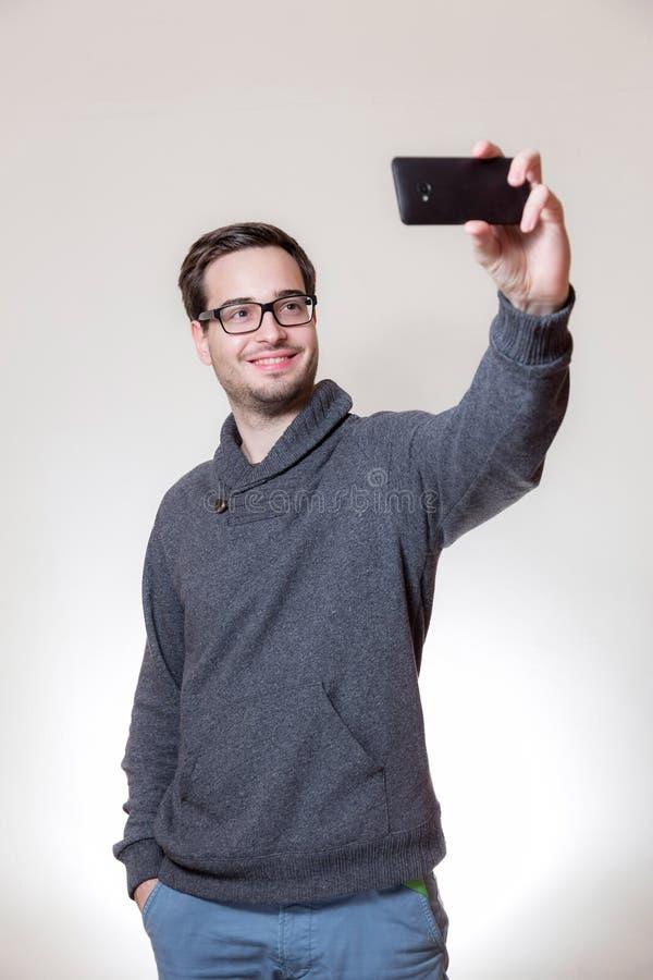 一个人采取与他的电话的一selfie 库存图片