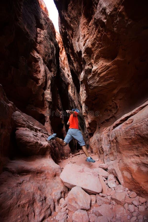 一个人从石头在詹妮` s峡谷跳在雪峡谷内 库存照片