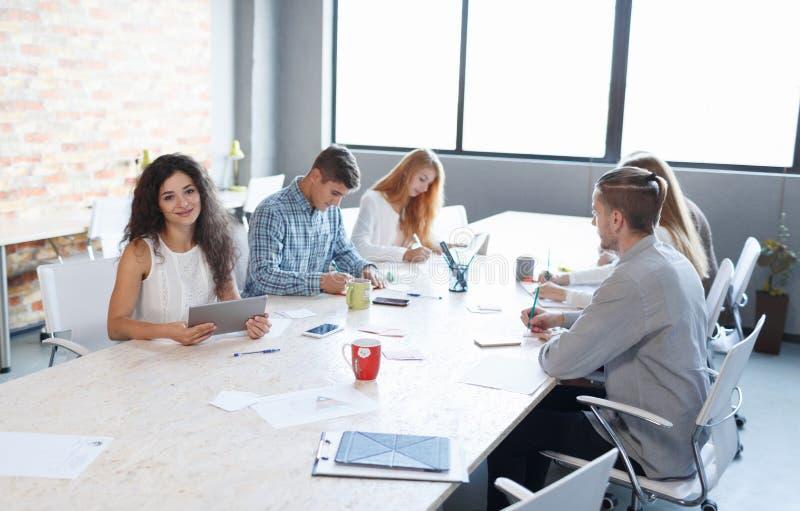 一个介绍的俏丽的妇女与在会议背景的办公室工作人员 概念另外现有量合伙企业编结难题二 复制空间 库存图片