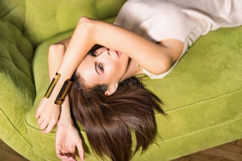 一个优雅的年轻女人在绿色沙发上摆姿势的肖像 免版税库存图片