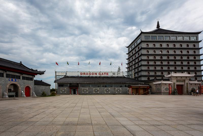 一个传统中国大厦和正方形在龙门 与多云天空的入口和旅馆大厦 库存照片