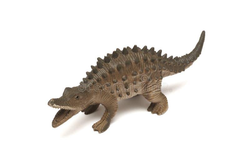 一个低后长的下颌恐龙玩具小雕象 免版税库存图片