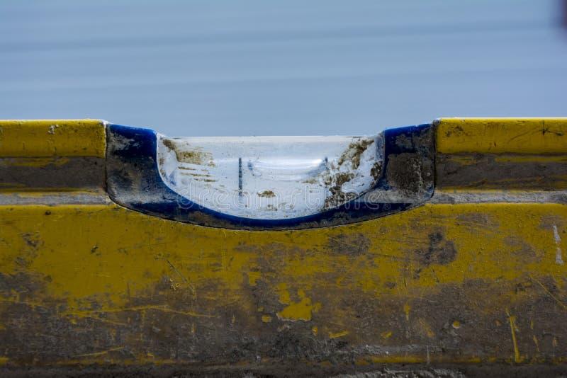 一个使用的和肮脏的水平仪的宏观图象在wal的混凝土的 库存照片