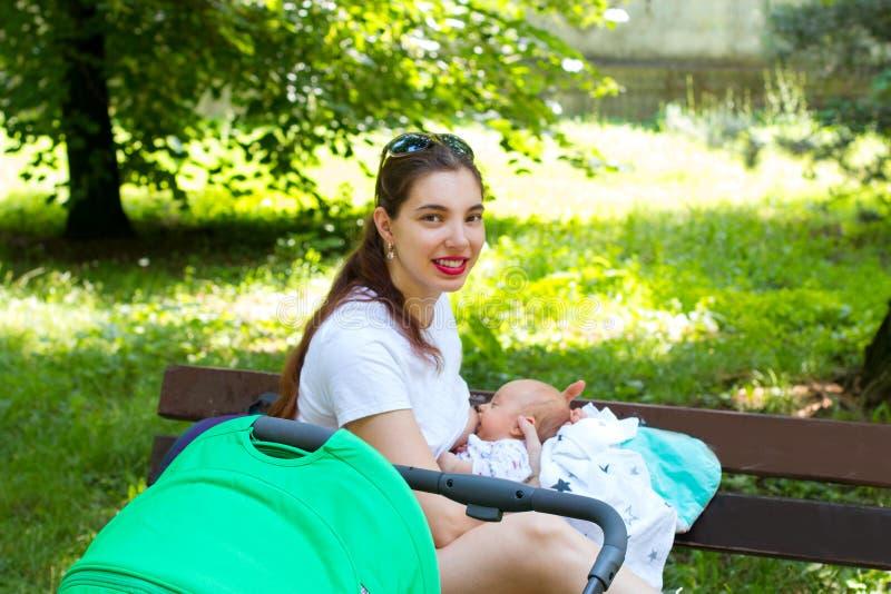 一个俏丽的养母和婴孩的画象,年轻妈妈外面与她的婴儿推车步行的婴儿,哺乳公众 库存照片