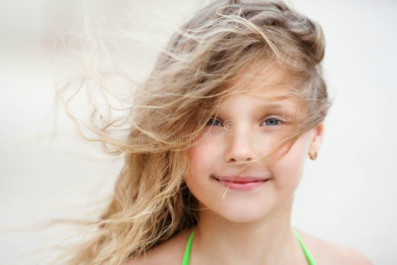 一个俏丽的微笑的小女孩的特写镜头画象有挥动的图片