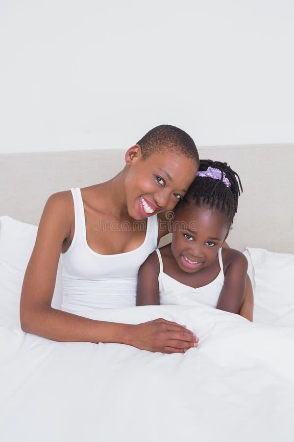 一个俏丽的母亲的画象有她的女儿的在床上 免版税库存图片