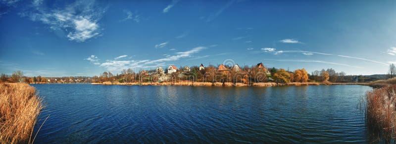 一个假日村庄的全景在一个大蓝色湖的另一边的 早期的春天或秋天 干燥芦苇,在边的薹 库存照片
