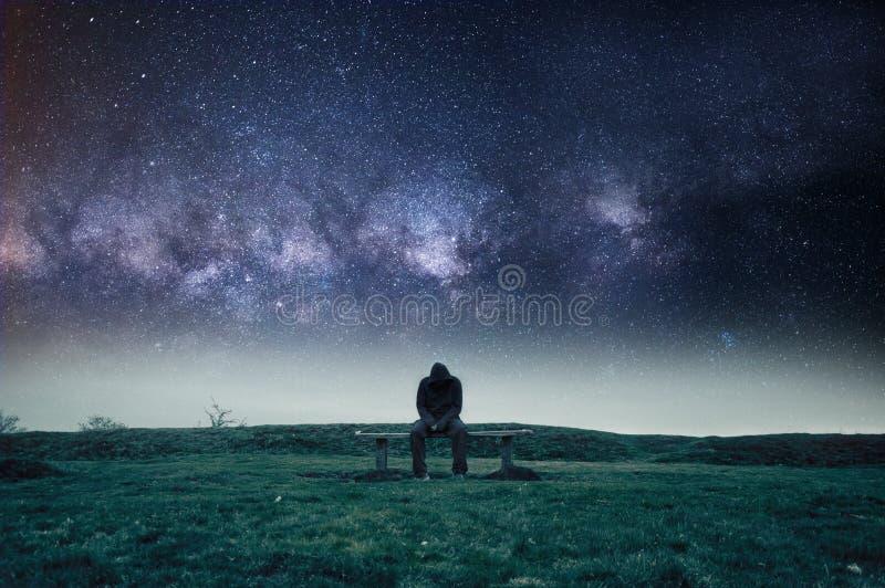 一个偏僻的戴头巾图坐公园长椅,看起来哀伤,偏僻和沮丧 上面星和宇宙 免版税库存图片