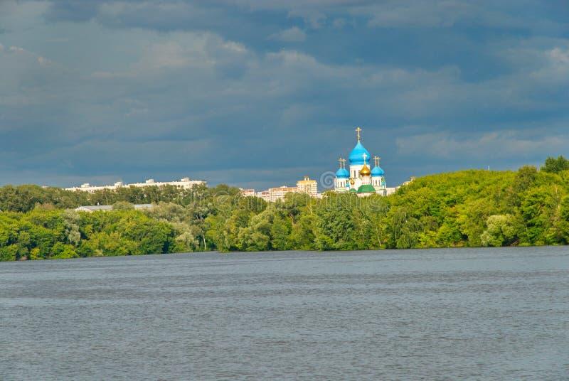 一个偏僻的教会能在树后被看见另一边河 库存图片