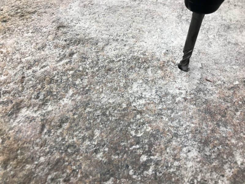 一个健壮,坚硬金属铁钻头操练在一块大灰色石头的一个孔 接近的视图 抽象背景异教徒青绿 免版税库存图片
