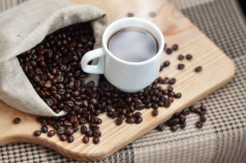 一个充分的袋子棕色咖啡豆和一个白色杯子热的咖啡l 库存照片