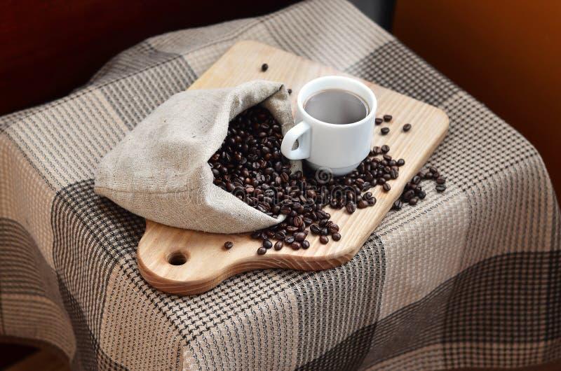 一个充分的袋子棕色咖啡豆和一个白色杯子热的咖啡l 库存图片