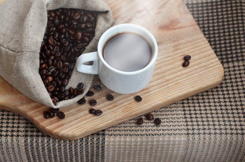 一个充分的袋子棕色咖啡豆和一个白色杯子热的咖啡l 免版税图库摄影