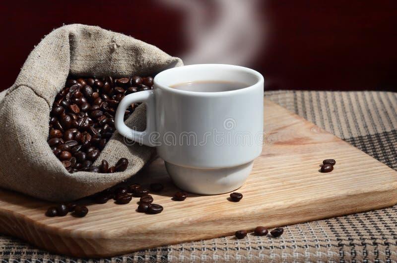 一个充分的袋子棕色咖啡豆和一个白色杯子热的咖啡l 免版税库存图片