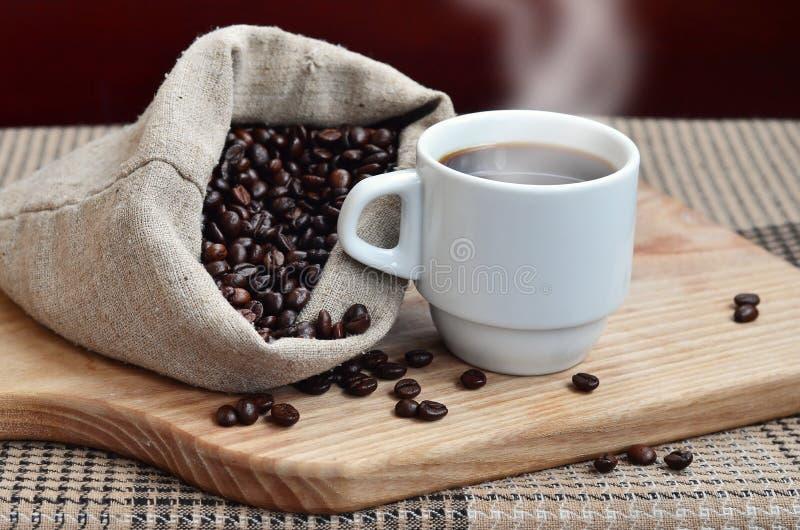 一个充分的袋子棕色咖啡豆和一个白色杯子热的咖啡l 图库摄影