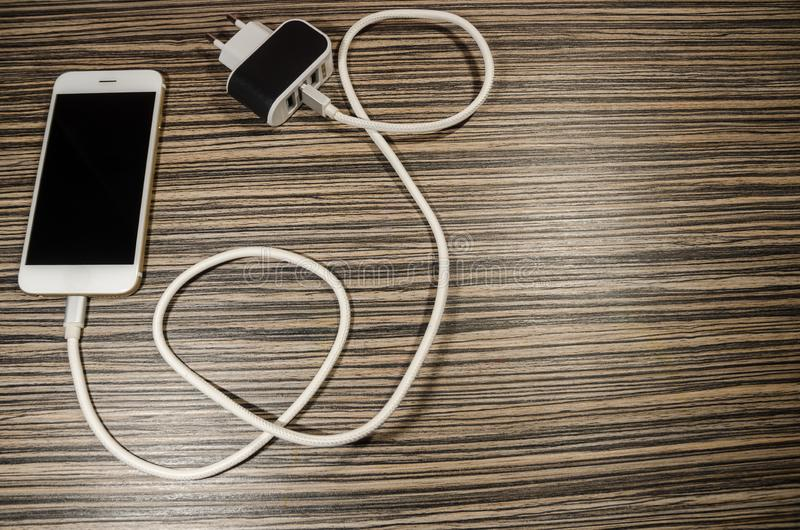 一个充电的电话和适配器块有关通过缆绳 库存图片