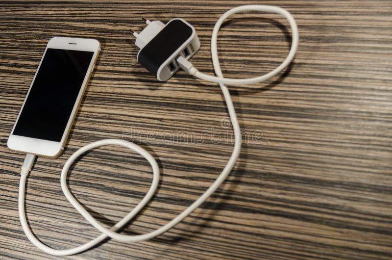 一个充电的电话和适配器块有关通过缆绳 库存照片