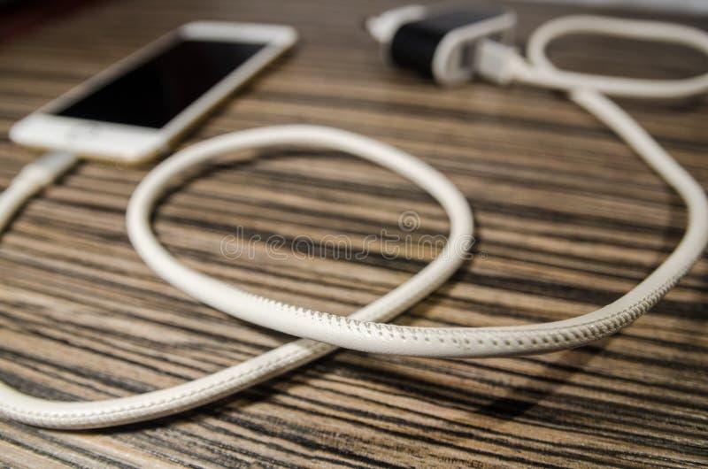 一个充电的电话和适配器块有关通过缆绳 免版税库存图片
