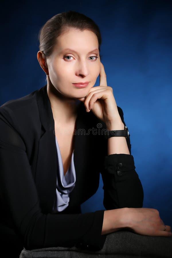 一个典雅的女商人的画象在蓝色背景的 库存照片