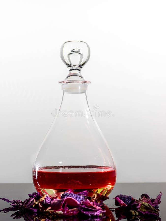 一个典雅的酒壶&一些五颜六色的干瓣反射性表面上 免版税图库摄影
