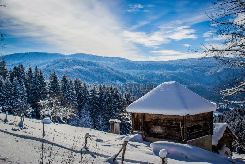 一个冬天和一好日子在山 老房子特写镜头和美好的冬天风景、天空蔚蓝和云彩在背景中 免版税库存图片