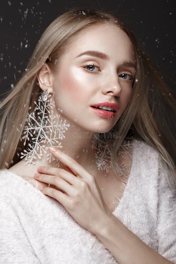 一个冬天图象的美丽的白肤金发的女孩与雪 秀丽表面 免版税库存照片