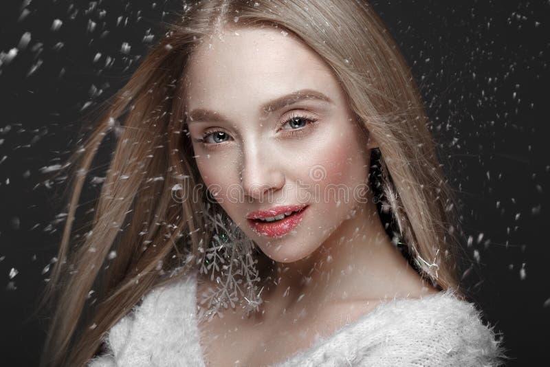 一个冬天图象的美丽的白肤金发的女孩与雪 秀丽表面 库存照片