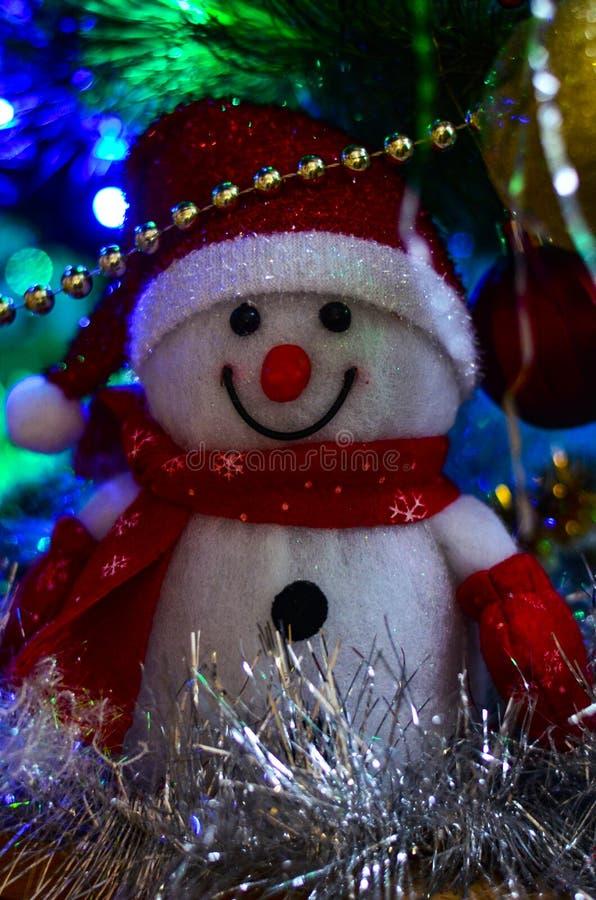 一个冬天白色玩具雪人的特写镜头与圣诞节闪亮金属片的在背景中 免版税图库摄影