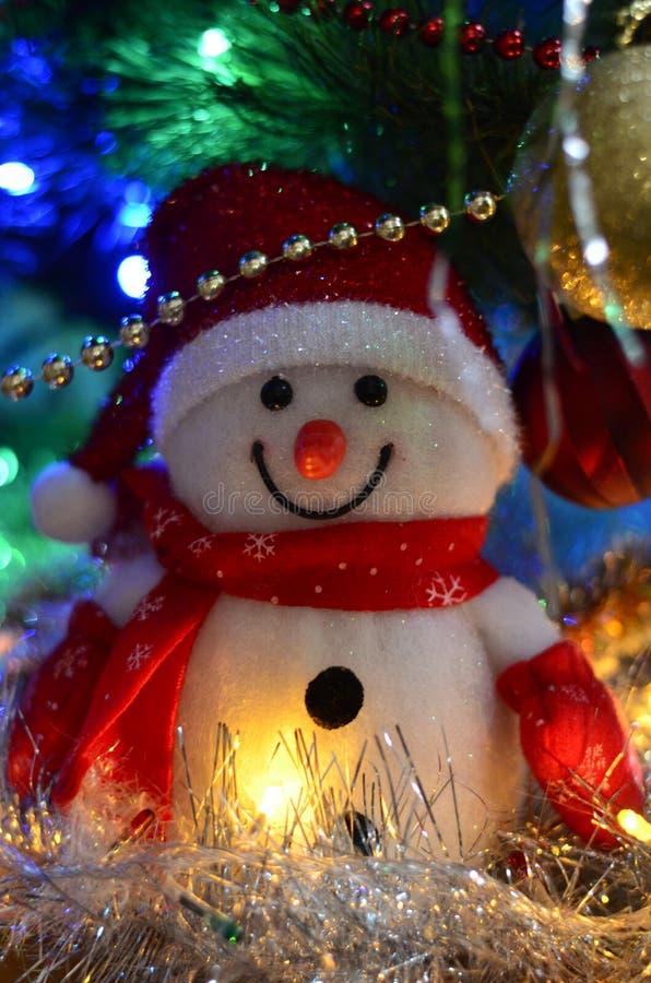 一个冬天白色玩具雪人的特写镜头与圣诞节闪亮金属片的在背景中 免版税库存照片