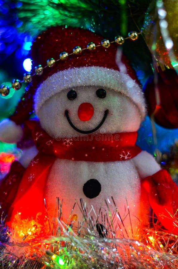 一个冬天白色玩具雪人的特写镜头与圣诞节闪亮金属片的在背景中 库存图片
