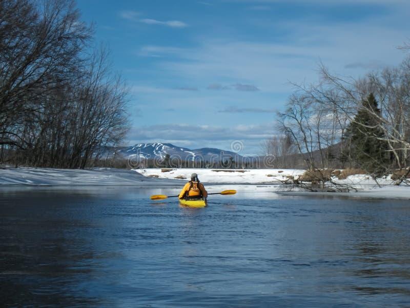 一个冰冷的湖的皮船冲浪者 免版税库存图片