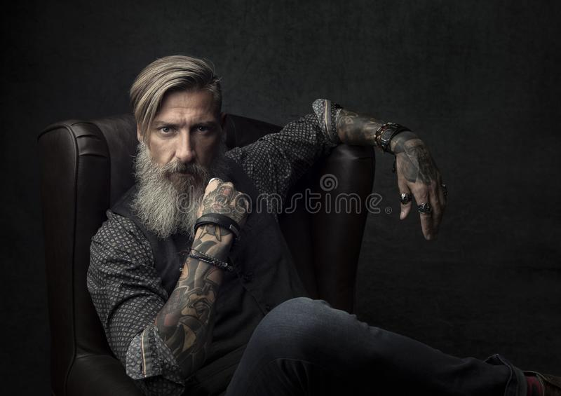 一个凉快的有胡子的商人的画象,坐扶手椅子 库存照片
