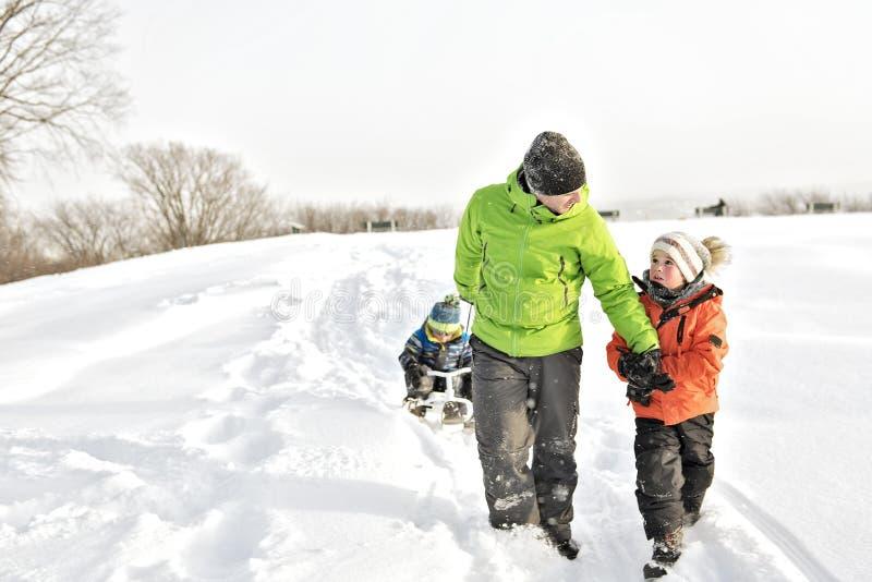 一个凉快的父亲扯拽他的雪撬的男孩 免版税库存图片