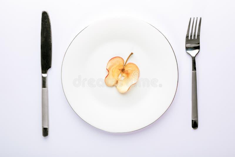 一个切片在白色板材的干苹果有在白色背景的利器的 库存照片