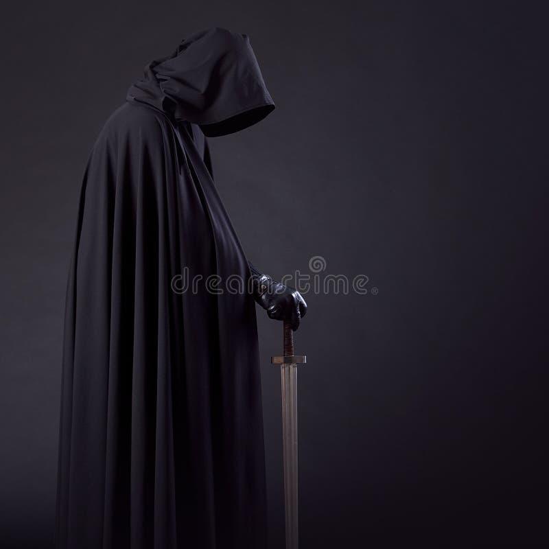 一个勇敢的战士流浪汉的画象一把黑斗篷和剑的在手中 免版税库存照片