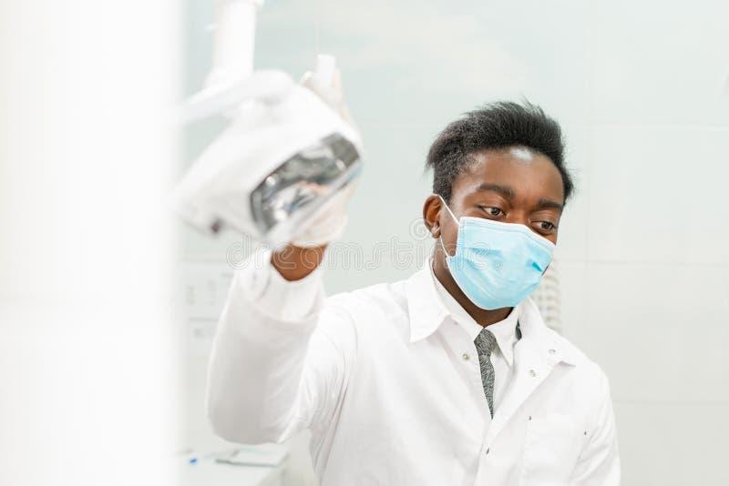 一个医疗面具的年轻非裔美国人的男性医生牙医 椅子的美女患者在牙齿诊所 医学 库存照片