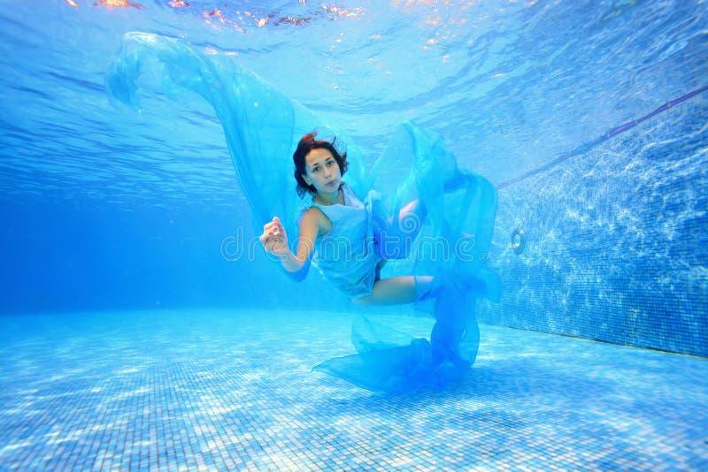 一个十几岁的女孩一件蓝色礼服的和有一块蓝色布料的在她的手上在水池游泳在水面下反对蓝色背景 图库摄影