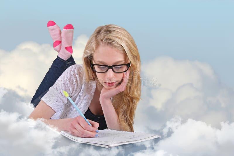 一个十几岁的女孩做在云彩的家庭作业 免版税库存图片
