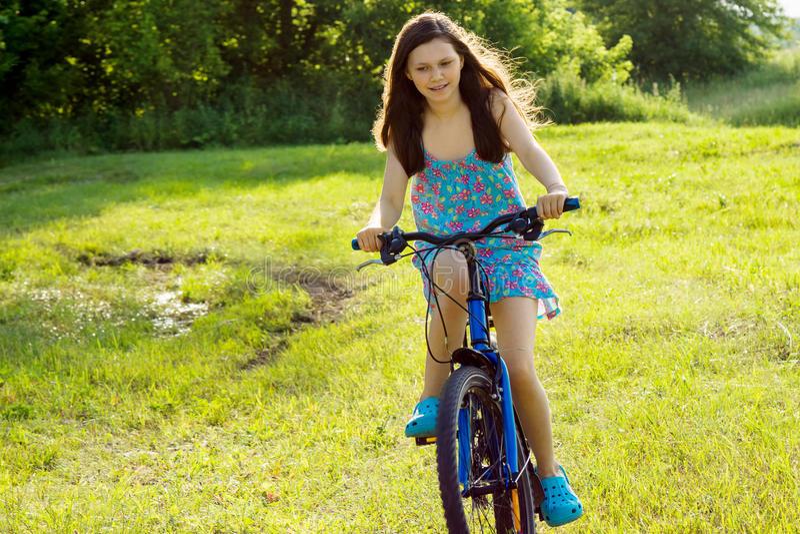 一个十几岁的女孩在草坪骑自行车 库存图片