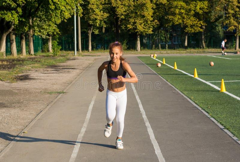 一个十几岁的女孩在踏车跑在学校体育场 免版税图库摄影