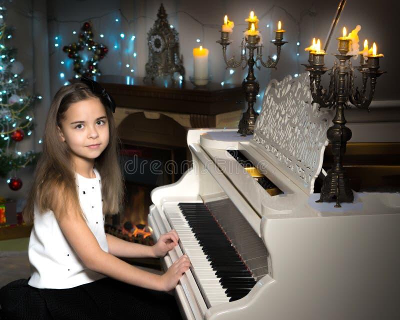 一个十几岁的女孩由烛光弹钢琴在圣诞夜 图库摄影