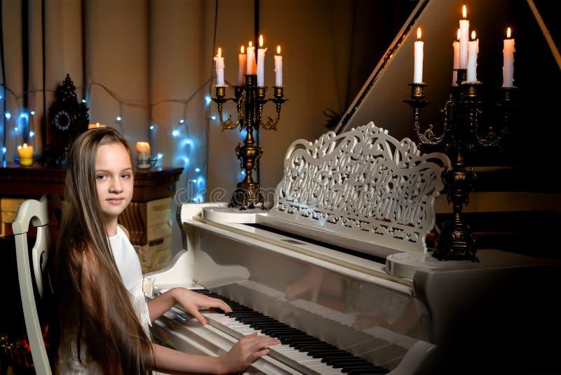 一个十几岁的女孩由烛光弹钢琴在圣诞夜 免版税库存照片