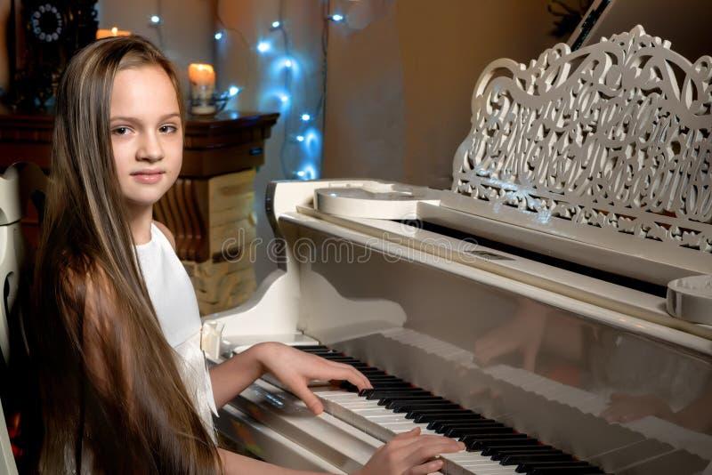 一个十几岁的女孩由烛光弹钢琴在圣诞夜 免版税库存图片