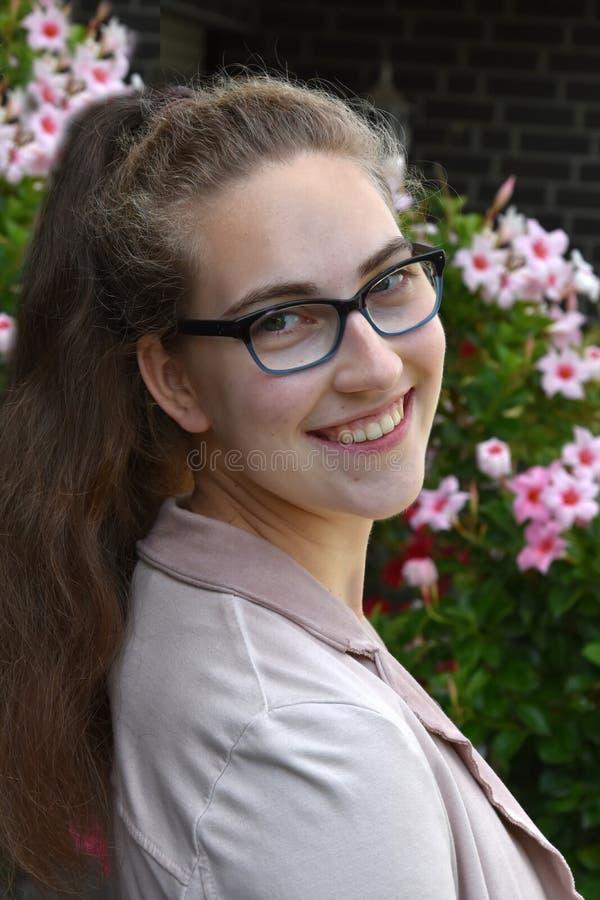 一个十几岁的女孩的画象戴眼镜的 库存照片