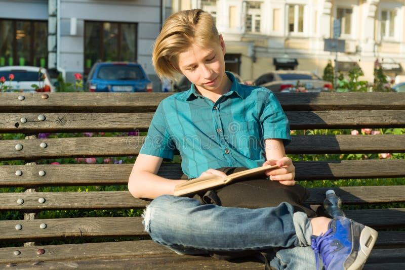 一个十几岁的男孩和女孩14, 15岁的室外画象,坐长凳在有书的城市公园 免版税库存图片